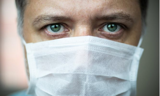 closeup-middleaged-greeneyed-doctor-with-mask-on-his-face-picture-id1215484559-666x399